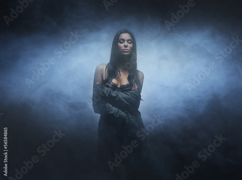 Fashion shoot of a young and sexy brunette on a dark background