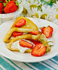 Pancakes with strawberries and daisies on a napkin