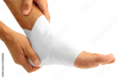 Young man with elastic bandage on leg, isolated on white