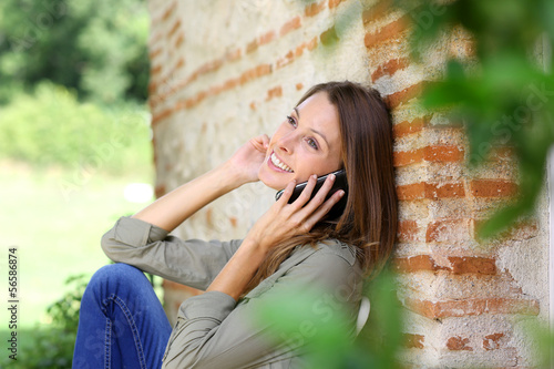 Sweet girl in home garden talking on the phone