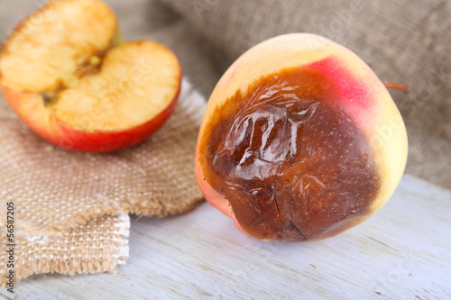 Rotten apples on wooden board on sackcloth