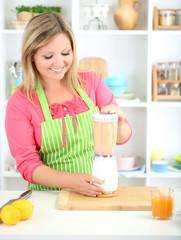Happy smiling woman in kitchen preparing fresh fruit cocktail