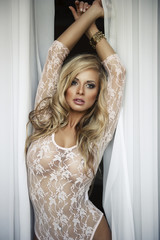 Sexy blonde woman with curtains