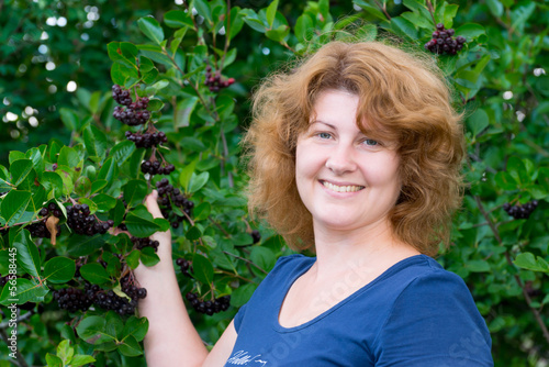 A woman in a black chokeberry bush in the garden