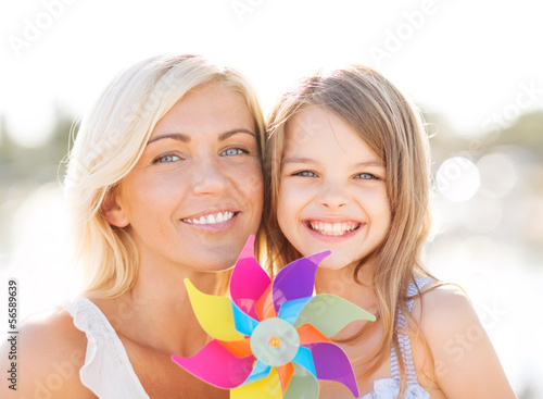 happy mother and child girl with pinwheel toy