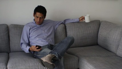 businessman sitting on sofa at home, talking on the phone