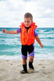 small boy in his diving suit and life jacket at the beach