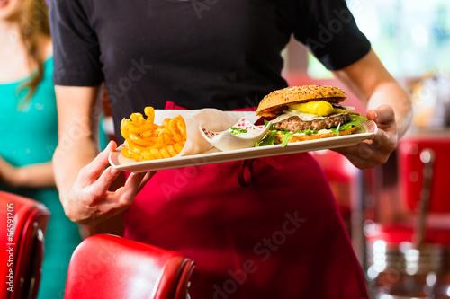 Leinwandbild Motiv Waitress serving in American diner or restaurant