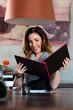 Woman in restaurant choosing food in menu