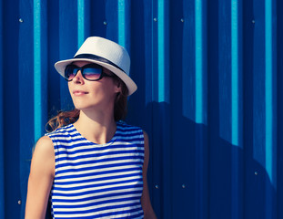 Attractive young woman in a hat and sunglasses at the wall.