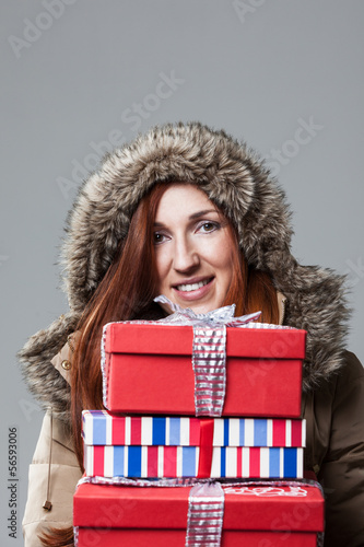 Pretty winter woman carrying Christmas gifts