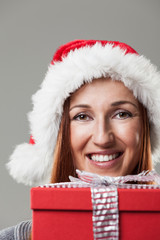 Woman in a Santa hat with a Christmas gift