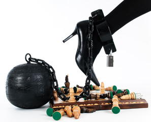female leg chained to the prison ball entering the game of chess