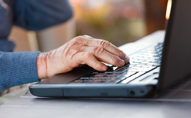 Old hand on a laptop
