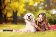 Beautiful female lying down with her dog in a park