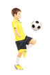 Child in sportswear joggling with a soccer ball
