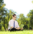 Young businessman working on a tablet in a park