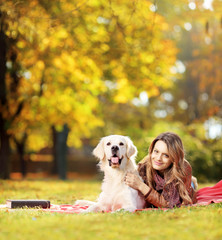 Young female lying down with her dog in a park