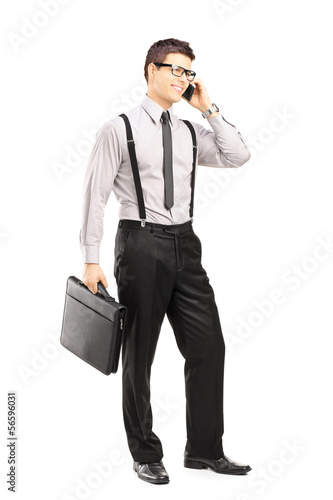 Young man holding a briefcase and talking on a phone