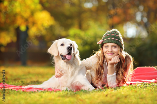 Pretty female lying down with her dog in a park