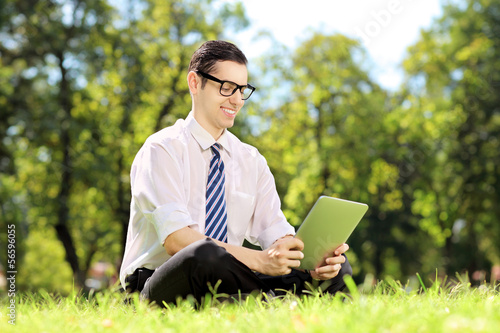 Businessperson with glasses seated on a grass working on tablet