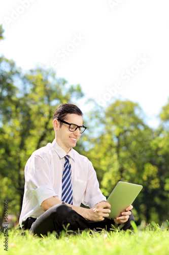 Young businessperson sitting on a grass and working on a tablet