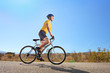 Young male with helmet riding a bike on a sunny day