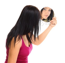 young woman looking at her face in mirror