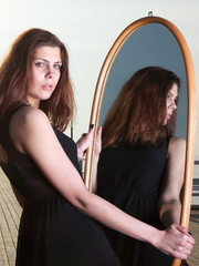 thoughtful woman looks at the reflection in mirror