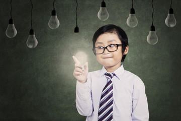Child holds a lit bulb under lamps