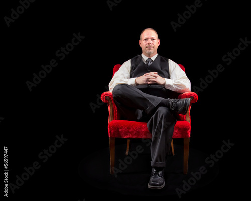 successful business man in vest sitting in red velvet chair