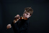 Virtuoso Teen Male Violinist on Dark Background Playing