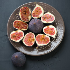 Sliced fig fruits on ceramic plate, view from above
