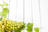 Grapes and leaves on vintage white planks background