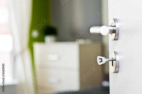 Detail of the key in the door with beautiful modern bedroom