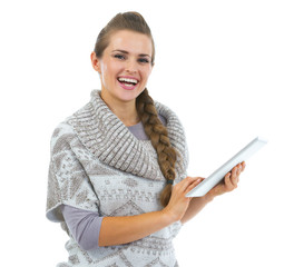 Smiling young woman in sweater using tablet pc