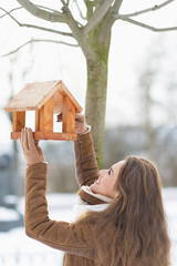 Happy young woman adding meal into bird feeder