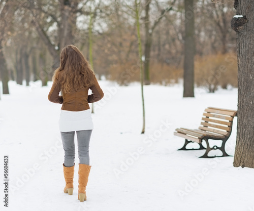 Woman walking in winter park . rear view