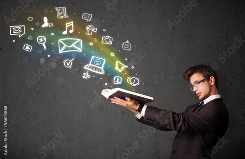 Young businessman reading a book with multimedia icons coming ou