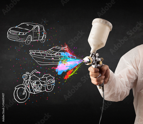 Man with airbrush spray paint with car, boat and motorcycle draw