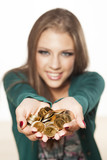 Happy attractive girl is holding bunch of coins in her hands