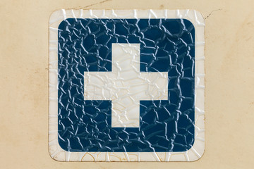 Retro styled image of a cracked blue cross label