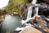 Trekker looks at wild waterfall in Horton Plains National Park,