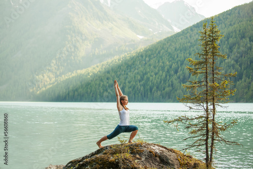 Tuinposter Gymnastiek Young woman is practicing yoga at mountain lake