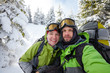 Two funnny hikers posing at camera in winter mountains