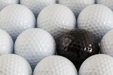 White golf balls and one black ball