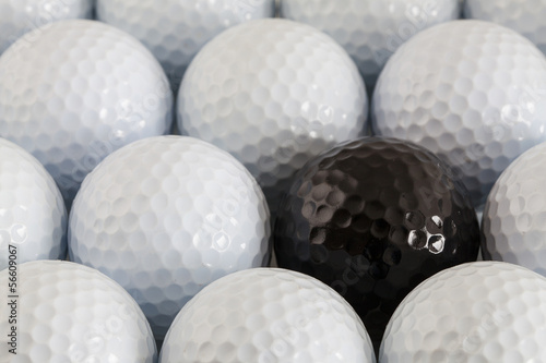 White golf balls and one black ball