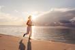 Caucasian woman jogging at the seashore