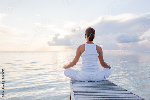 Leinwanddruck Bild Caucasian woman practicing yoga at seashore