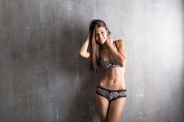 Sexy girl in lingerie with lace brindle, textural on a gray back